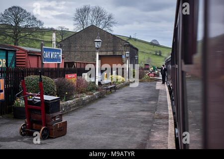 Oakworth, West Yorkshire / UK - March 24th 2018: A vintage steam train pulls off to Oakworth station on the Worth Valley railway in West Yorkshire - Stock Photo