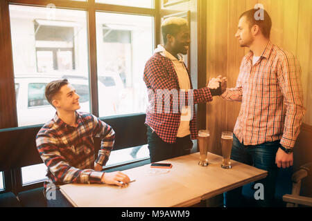 Happy to finally meet old male friends in bar. Shaking hands and smiling. - Stock Photo