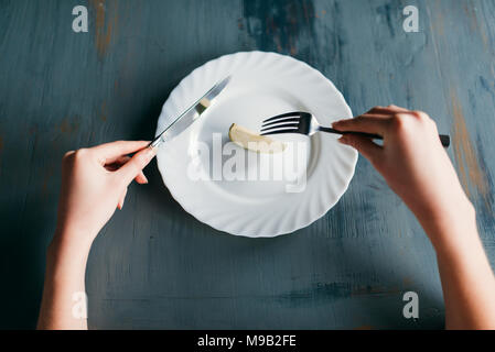 Female person against plate with a slice of apple - Stock Photo