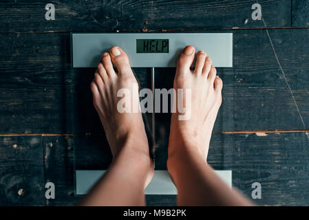 Female feet on the scales with inscription help - Stock Photo