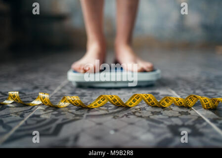 Female feet on the scales, measuring tape - Stock Photo