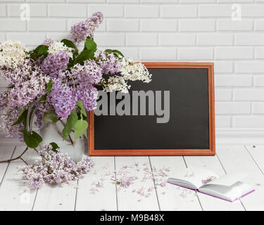 Beautiful bouquet of white and violet lilac flowers in glass vase with opened pad and black chalkboard,on the white wooden and brick background with e - Stock Photo