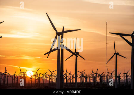 Power generating windmills in the Coachella valley of Southern California at sunset - Stock Photo
