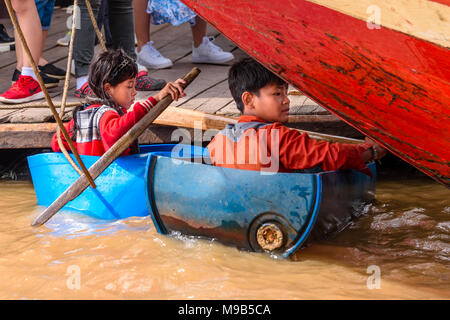 Two young children float in plastic barrels to beg for money from tourists at the floating village on the Siem Reap river, Cambodia - Stock Photo