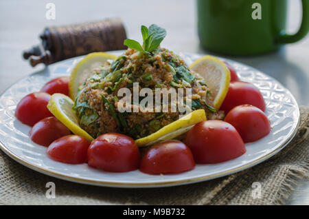 Salad with vegetables, lettuce, green onion, tomato paste, oil, and bulgur and tomato - Stock Photo