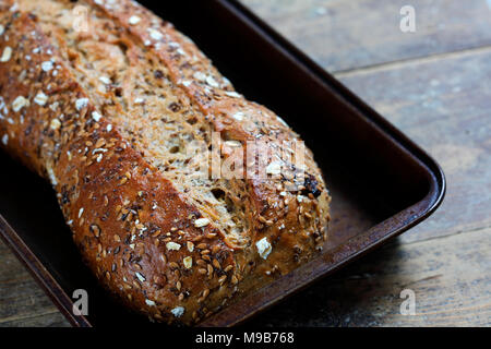 Rustic whole grain bread loaf in baking tray on wooden table - Stock Photo