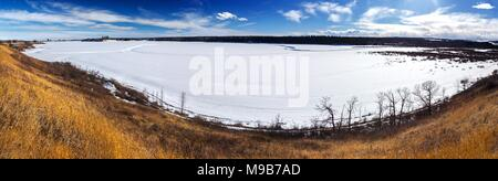Scenic Wide Panoramic Landscape View Snowy Frozen Glenmore Reservoir, Natural Prairies Grassland and Rocky Mountains Foothills Calgary Alberta Canada - Stock Photo