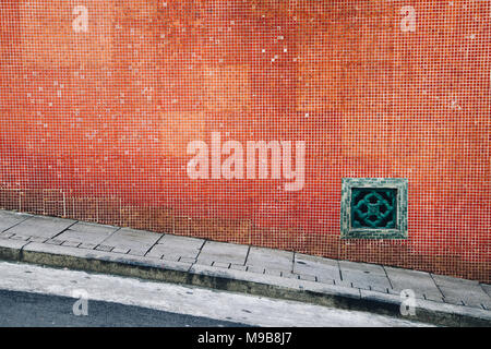 Old red tile wall and sloping street in Hong Kong - Stock Photo