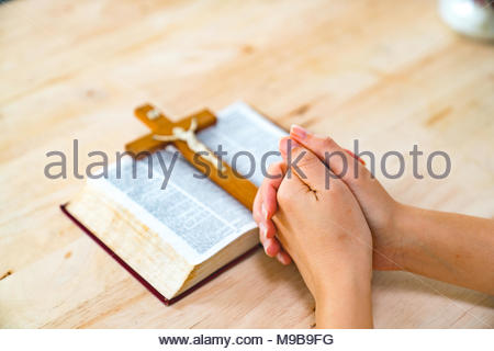 Christian woman praying with hands crossed and Holy Bible by his side on wooden desk in church, top view - Stock Photo