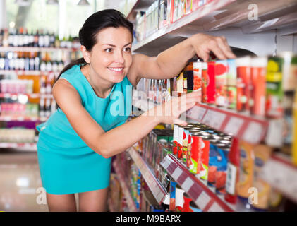Positive woman readig label on jar of tomato sauce at the supermarket - Stock Photo