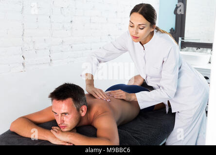 Professional masseuse performing back massage to positive swedish male client in spa center - Stock Photo