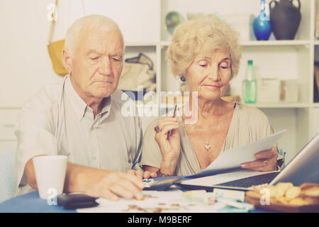 Serious senior couple counting money for paying bills with laptop at home - Stock Photo