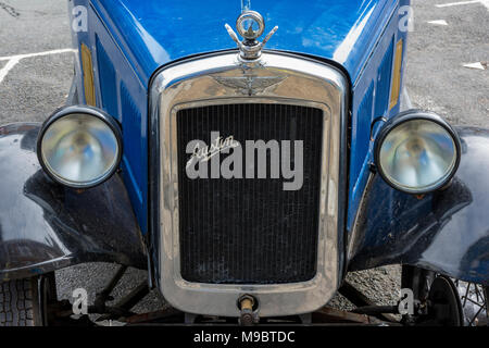 the radiator grill and badge with headlights on an old vintage austin car with chrome. front of a classic and vintage austin collectors classic car. - Stock Photo