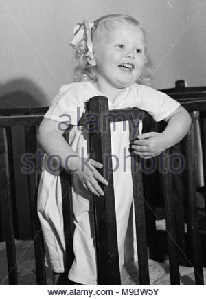 Life at the Tapley Park Children's Home, Instow, Devon, October 1942 A young smiling girl stands in her cot just before bedtime at the Chaim Weizmann Home, at Tapley Park, Instow, North Devon, October 1942. - Stock Photo