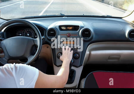 Woman adjusting volume at car audio system while she is driving. Cause of Distracted Driving Accidents concept. Inside car view - Stock Photo