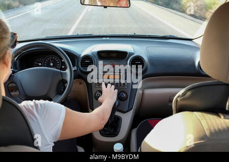Woman adjusting radio dial button control while she is driving. Cause of Distracted Driving Accidents concept. Inside car view - Stock Photo
