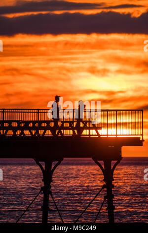 Aberystwyth Wales UK, Saturday 24 March 2018  UK Weather: People are silhouetted standing on the end of Aberystwyth pier  as the sun sets spectacularly over  Cardigan Bay ,  on the eve of British Summer Time, when the clocks go forwards and hour tonight  photo © Keith Morris  / Alamy Live News - Stock Photo