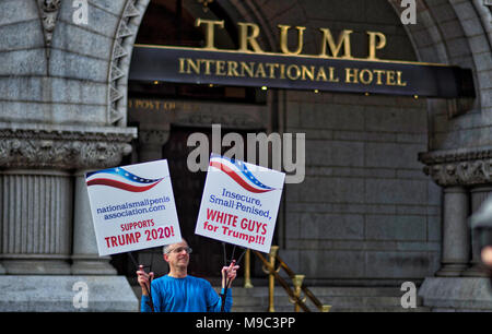 Washington DC, USA, March 24, 2018: A lone protester stand in front of the Trump International Hotel during the March for Our Lives rally on March 24, 2018 in Washington, D.C. Hundreds of thousands rallied in the nation's capital to demand action to end gun violence and mass shootings in schools. ( Credit: William Graham/Alamy Live News - Stock Photo