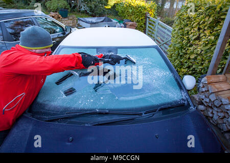 A man scraping ice of a frozen windscreen wearing hat and gloves in the rural village of Lixwm, Wales, UK - Stock Photo