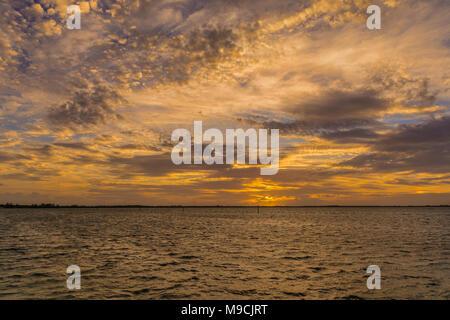 Early morning Bahamian sunrise featuring gorgeous colorful high contrast sky with colorful clouds - Stock Photo