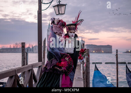 Romantic couple in costume and masks standing with back to the Grand Canal, gondolas and San Giorgio in the background, during Venice Carnival - Stock Photo