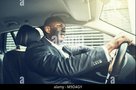 Smiling African businessman wearing a blazer driving through the city during his morning commute to work - Stock Photo