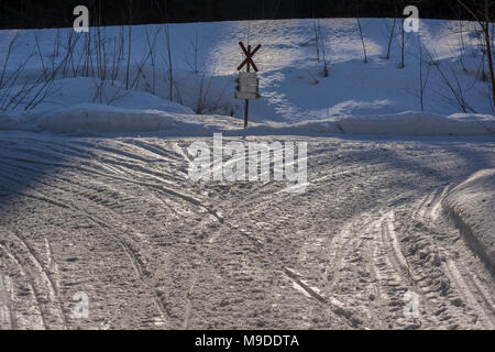 snowmobile trail crossing with a sign in the middle, picture from the Northern Sweden. - Stock Photo