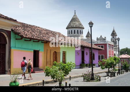 Couple sightseeing in the colourful colonial town of Granada in Nicaragua,  Iglesia de Guadalupe church on the right - Stock Photo