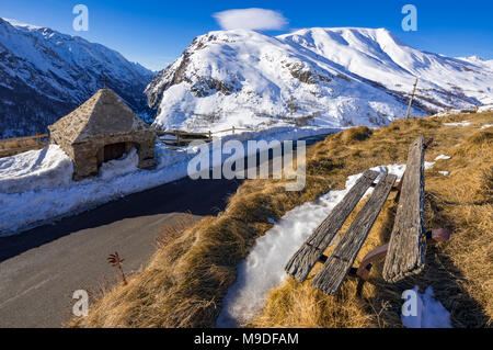 The roadside Oratory of Le Chazelet and an old wooden bench in winter. Ecrins National Park, PACA Region, Hautes-Alpes, Alps, France - Stock Photo