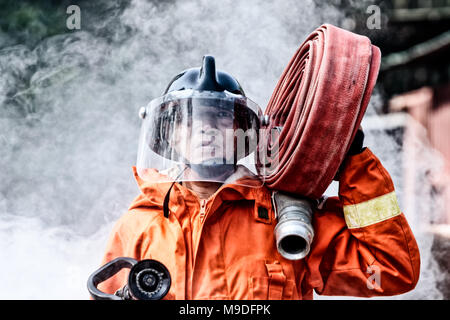 Emergency Fire Rescue training, firefighters in uniform,  carry a water hose run through flame - Stock Photo