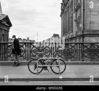 EDINBURGH, SCOTLAND - FEBRUARY 5TH 2018: Man walking passing a bike on George IV Bridge. - Stock Photo