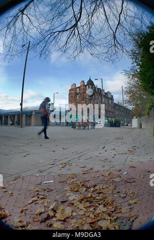 EDINBURGH, SCOTLAND - NOVEMBER 4TH 2009: A woman strolling towards the Morningside clock in Edinburgh. - Stock Photo