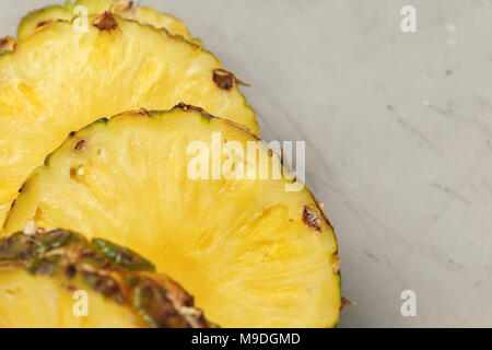 Fresh sliced pineapple on a white wooden cutting board. Concrete table backround. Top view - Stock Photo