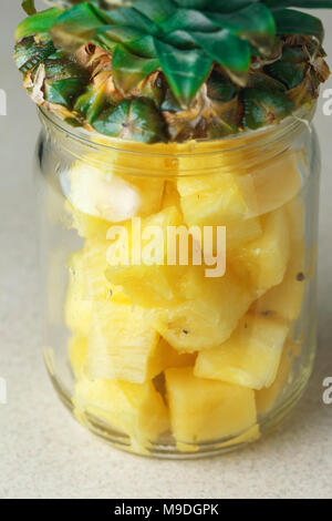 Fresh juicy pineapple pieces in a glass jar on the kitchen table against grey rile background - Stock Photo