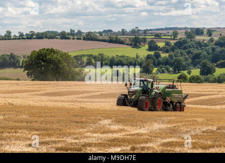 Tractor bailing straw in a newly harvested wheat field on a sunny day - Stock Photo