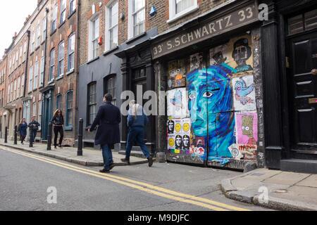 Street art on the gates to S. Schwartz at 33 Fournier Street, Spitalfields, London, E1, UK - Stock Photo