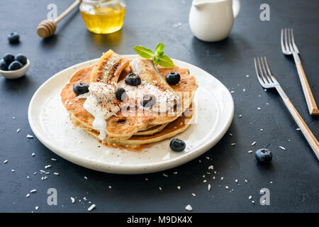 Oat pancakes with greek yogurt, roasted banana, blueberries and cinnamon on white plate - Stock Photo