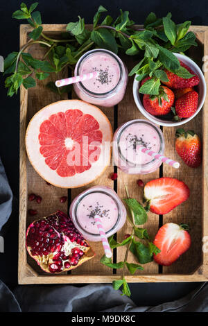 Fresh smoothies of strawberry, grapefruit and pomegranate in bottles. Top view. Healthy lifestyle, vegan, vegetarian, fitness concept - Stock Photo