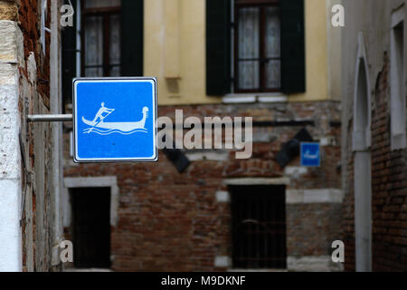 Two Gondola signs sit on a side-canal off the Grand Canal near the Rialto Bridge in Venice, Italy - Stock Photo