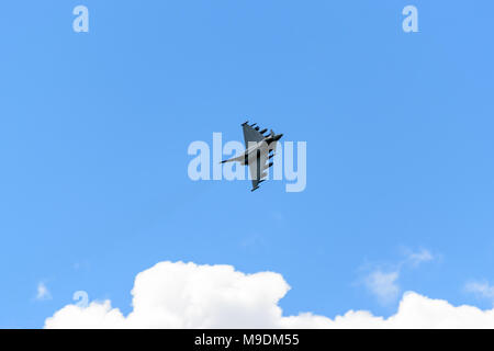 farnborough Airshow 2016: a Eurofighter Typhoon banks hard above some cloud - Stock Photo