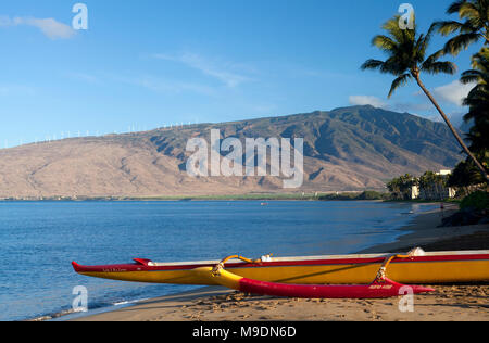 Outrigger canoe at Sugar Beach, Kihei, Maui, Hawaii.  The West Maui Mountains are in the background. - Stock Photo