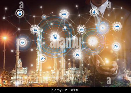 Double exposure of businessman hand hold smartphone working with oil refinery industry plant and industry icons. Factory in the night as communication - Stock Photo