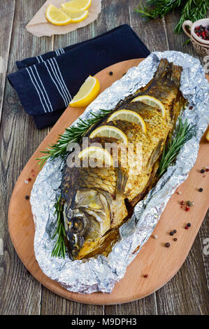Large baked carp with herbs, lemon and spices in foil on a wooden background. Top view - Stock Photo