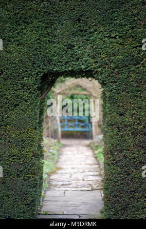 natural arch doorway entrance in hedge in ornamental garden - Stock Photo