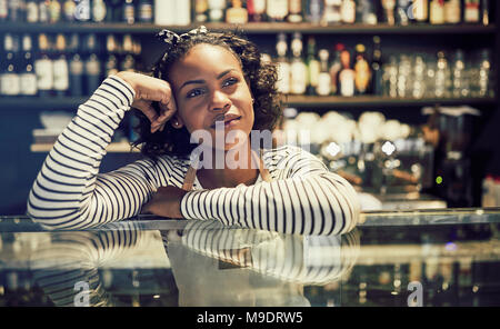 Smiling young African cafe owner looking deep in thought while leaning on the counter of her trendy cafe