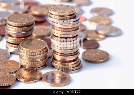 Many euro coins stacked in columns on white background. - Stock Photo
