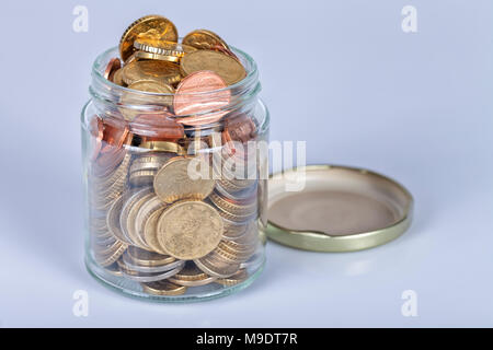 A glass jar full of euro coins on white background. - Stock Photo