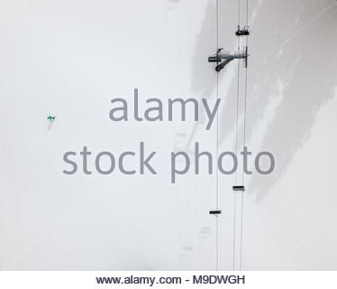 A skier and a ski chair lift cast shadows on the ski trail. - Stock Photo