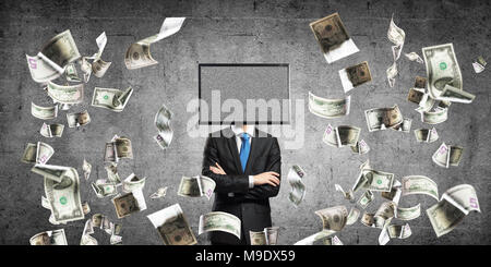 Businessman in suit with TV instead of head keeping arms crossed while standing among flying dollars and against gray dark wall on background. - Stock Photo