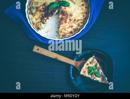 A piece of French quiche Lorraine pie from chicken, mushrooms and broccoli with basil on the spatula and plate on wooden background. Horizontal. Top v - Stock Photo
